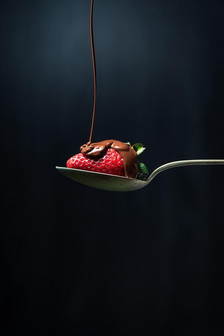 Schokolade fließt auf Erdbeere auf Löffel