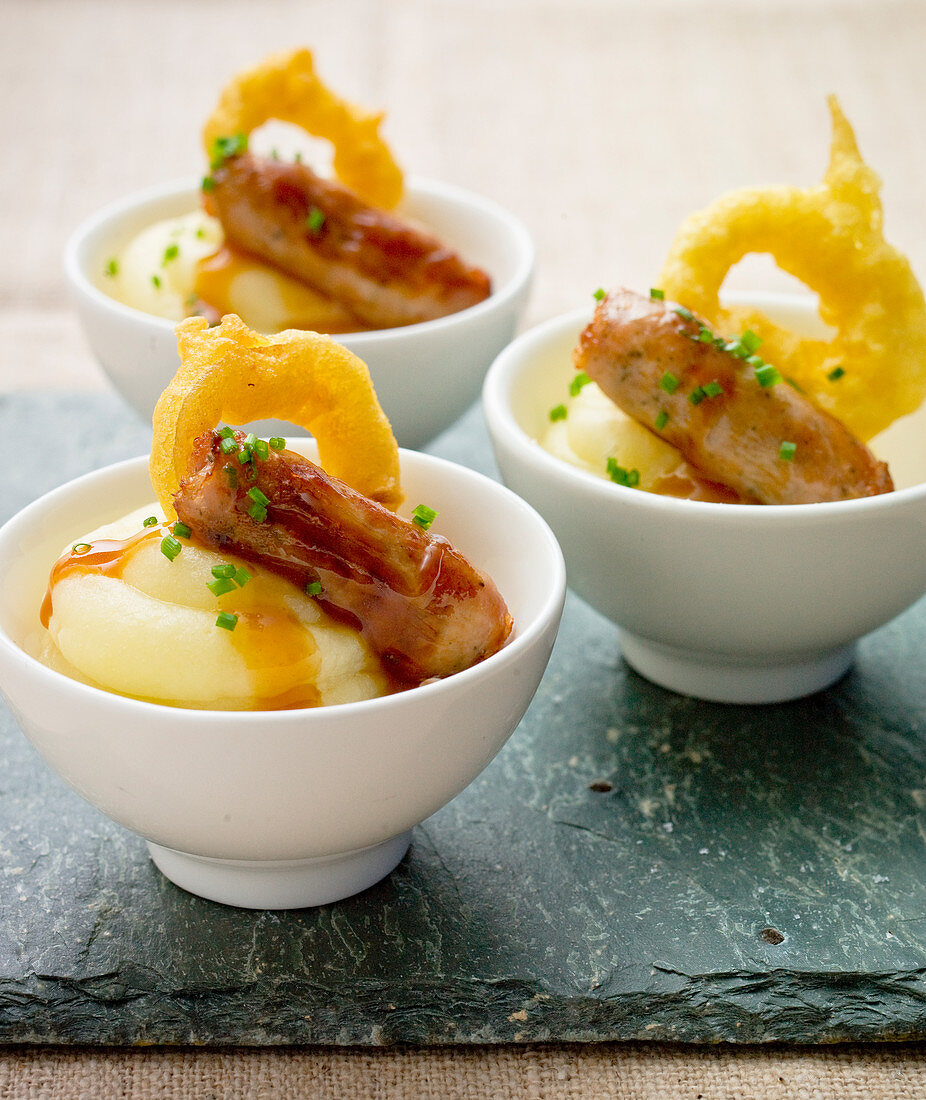 Sausage and mash potato, with an onion ring hors d'oeuvre (appetizer)