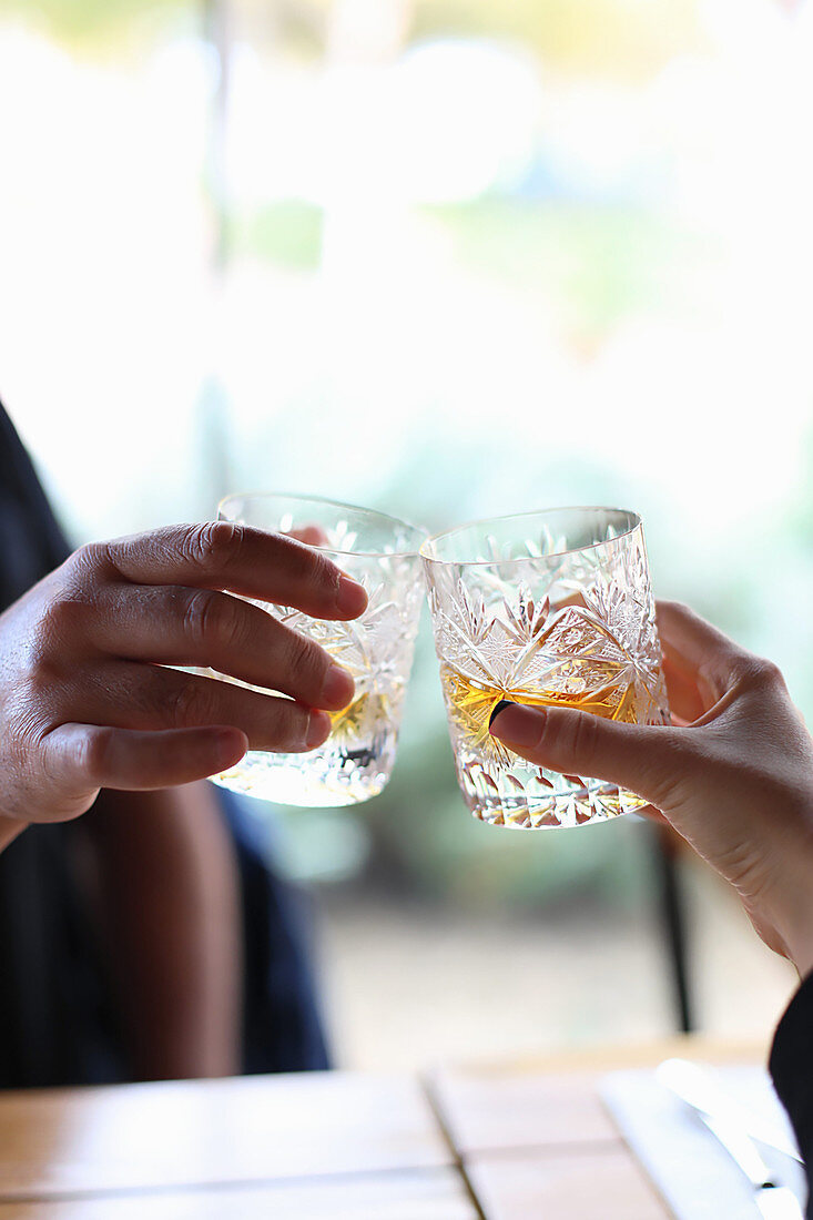 Two glasses with whiskey in hands of man and woman