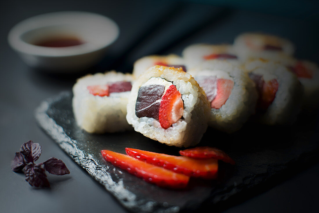 Sushi roll with strawberry, tuna and cream cheese, brawn crystal sugar on the top