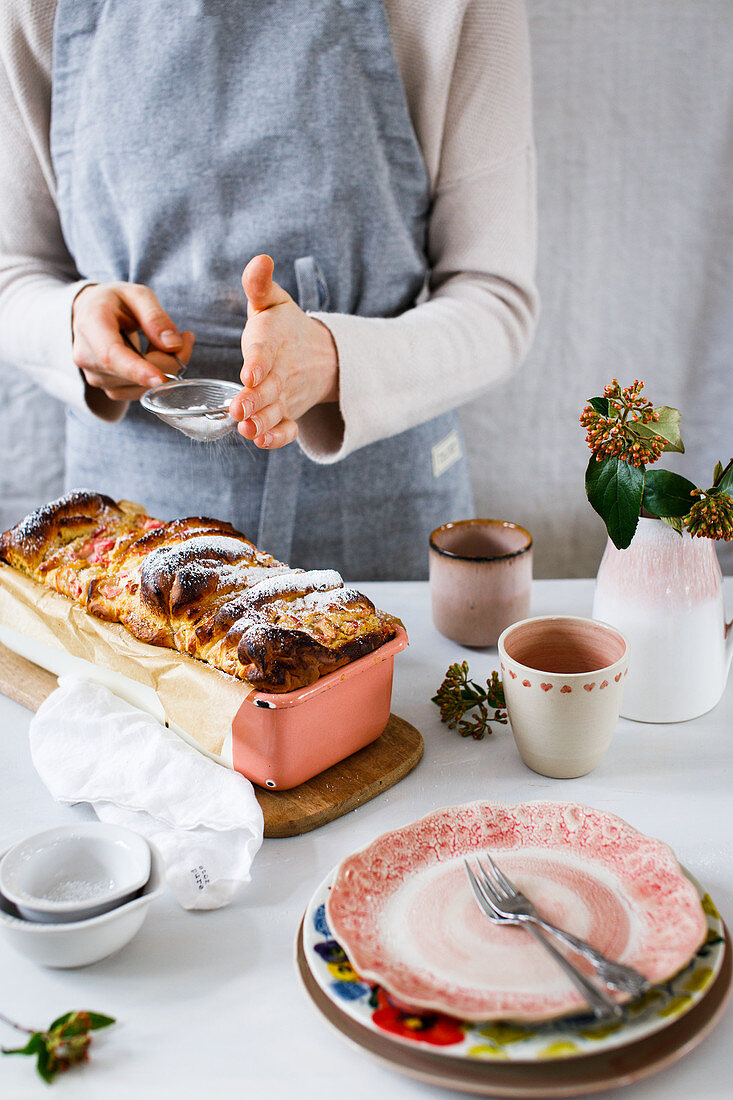 Pull-apart quark bread with rhubarb being dusted with icing sugar