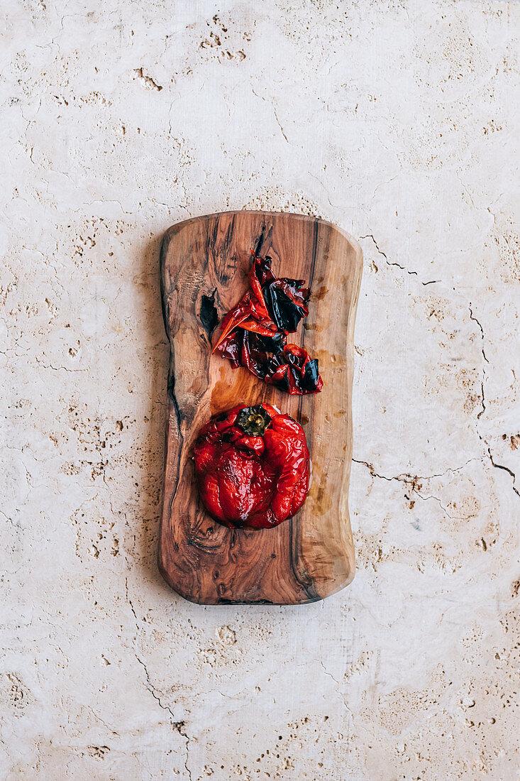 Gegrillte Paprika auf Holzbrett, teilweise gehäutet