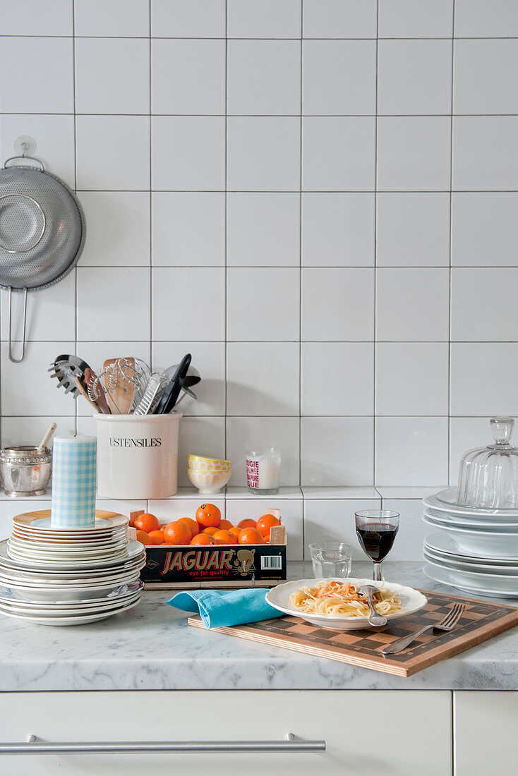 Chessboard used as tray in white kitchen with marble worksurface