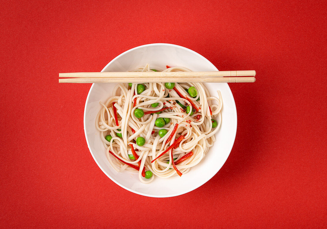 Asian noodles with vegetables, green peas and red pepper in white bowl with wooden chopsticks