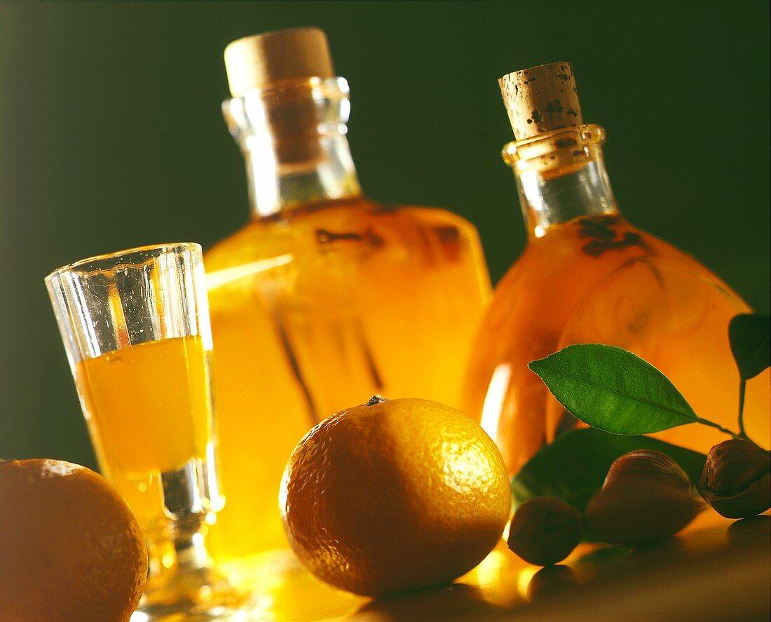 Orange liqueur in glass and carafes, decor: mandarins, nuts