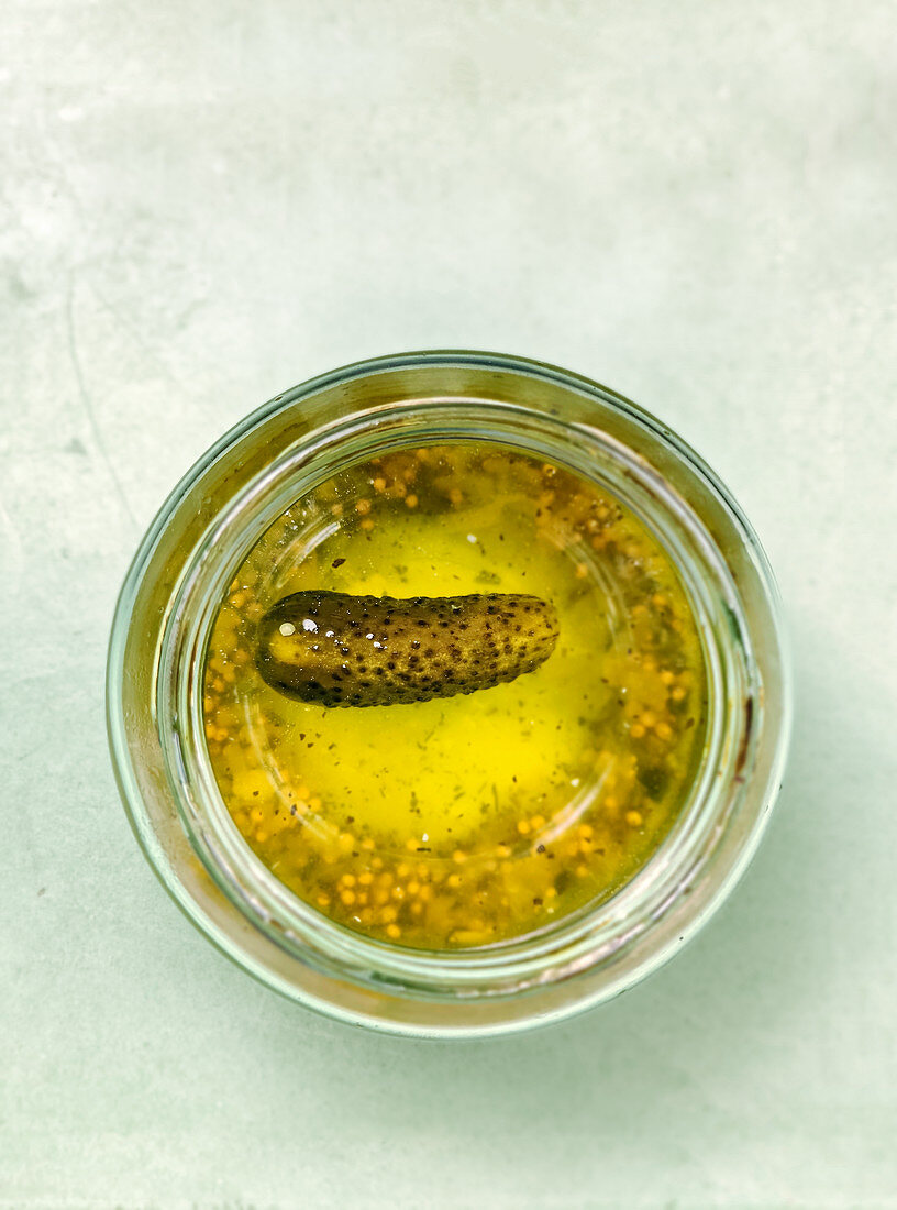 A gherkin in a preserving jar seen from above