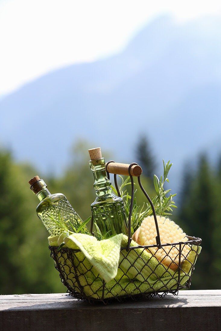 Homemade rosemary massage oil in wire basket
