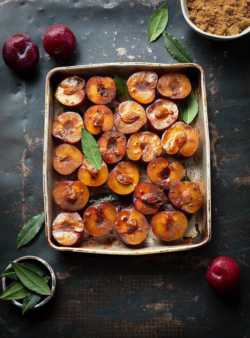 Sliced plums with cinnamon in roasting tray