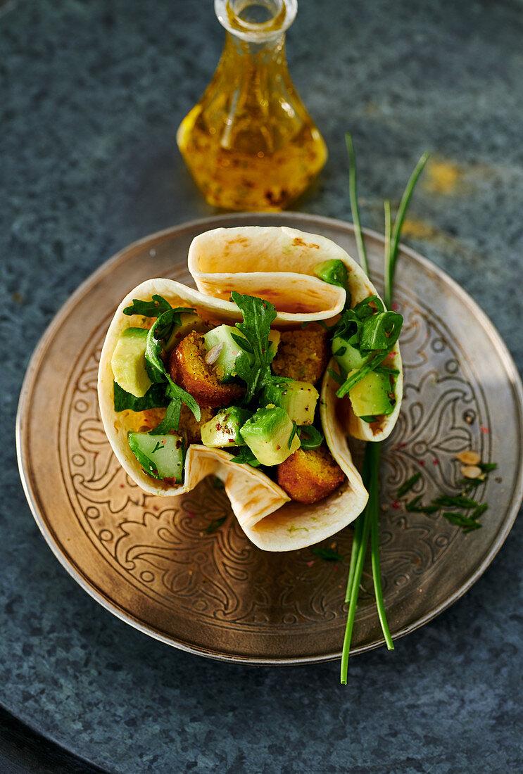 Falafel with an avocado salad in a wrap basket