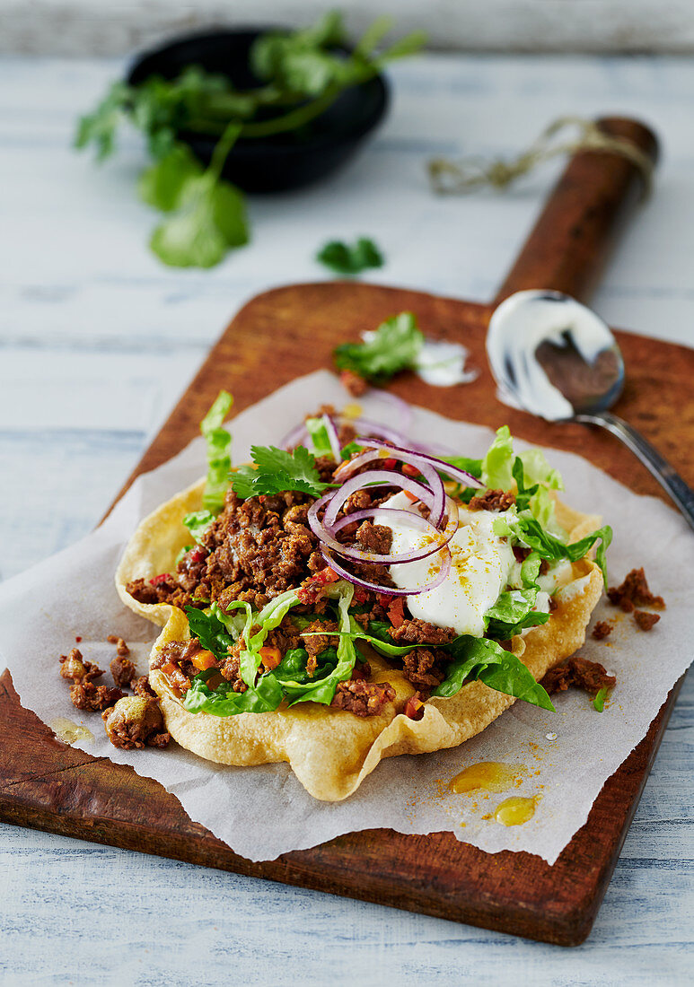 A poppadom topped with vegan mince and lettuce