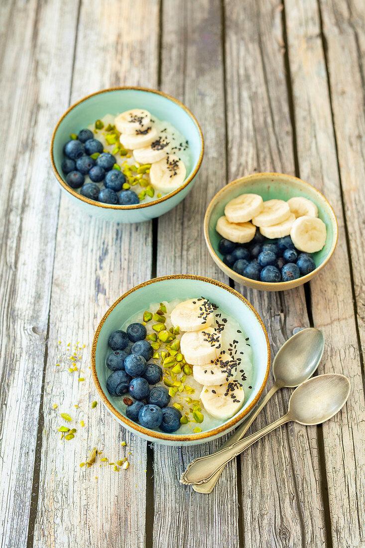 Sweet congee (rice porridge) with coconut water, banana and blueberries