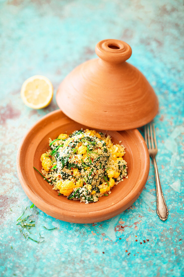 Couscous with yellow cauliflower, spinach and mint in a tagine (vegan)