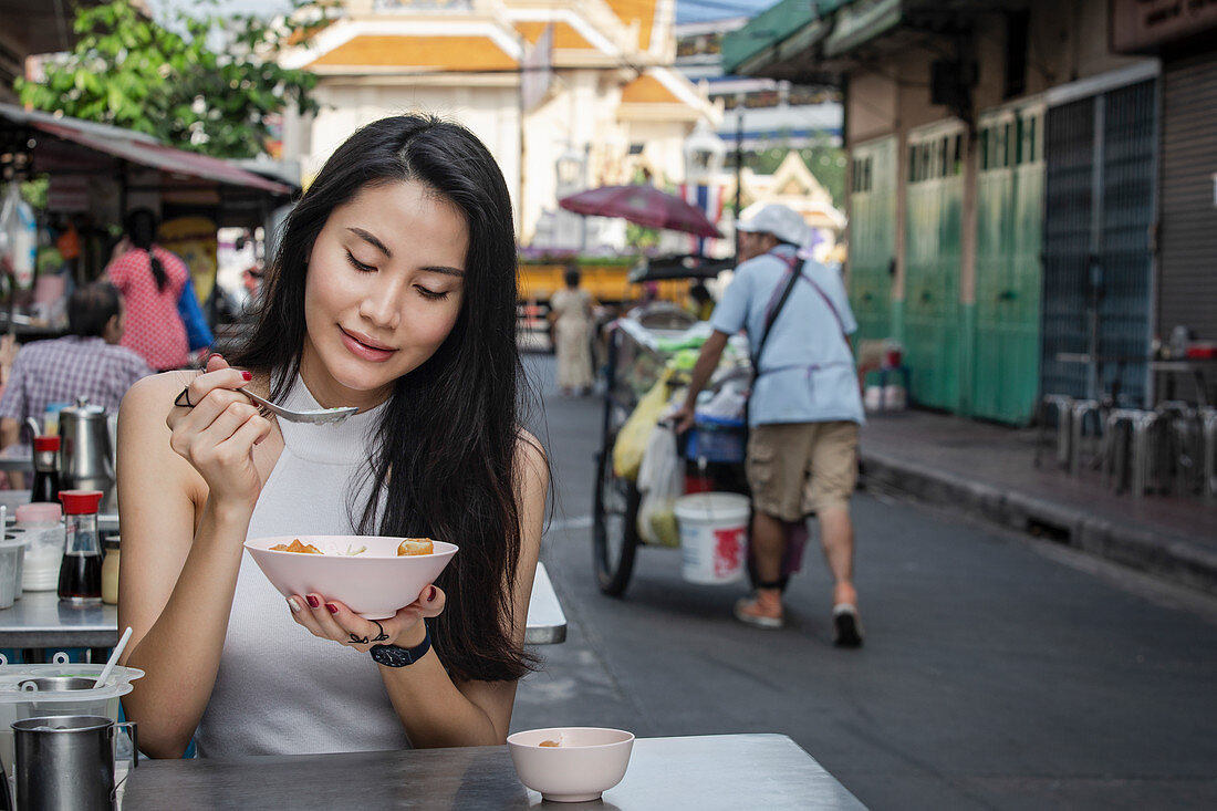 A young East Asian woman eating savoury congee (rice porridge) for breakfast