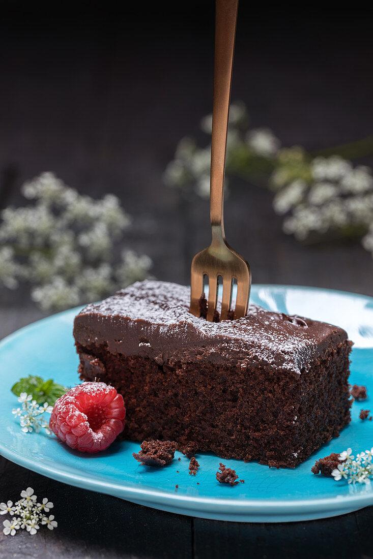Brownie with powder sugar and raspberries