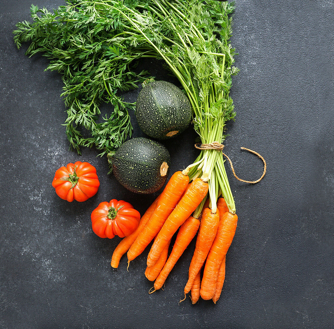 Carrots, tomatoes and zucchini on black background