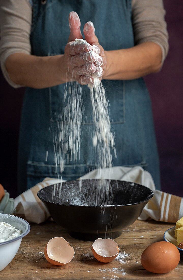 Spilling wheat flour into bowl near egg egg shells while preparing pastry at home