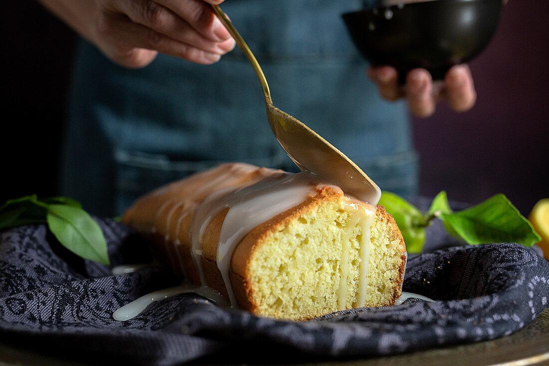 Zuckerglasur auf hausgemachten Zitronenkuchen träufeln