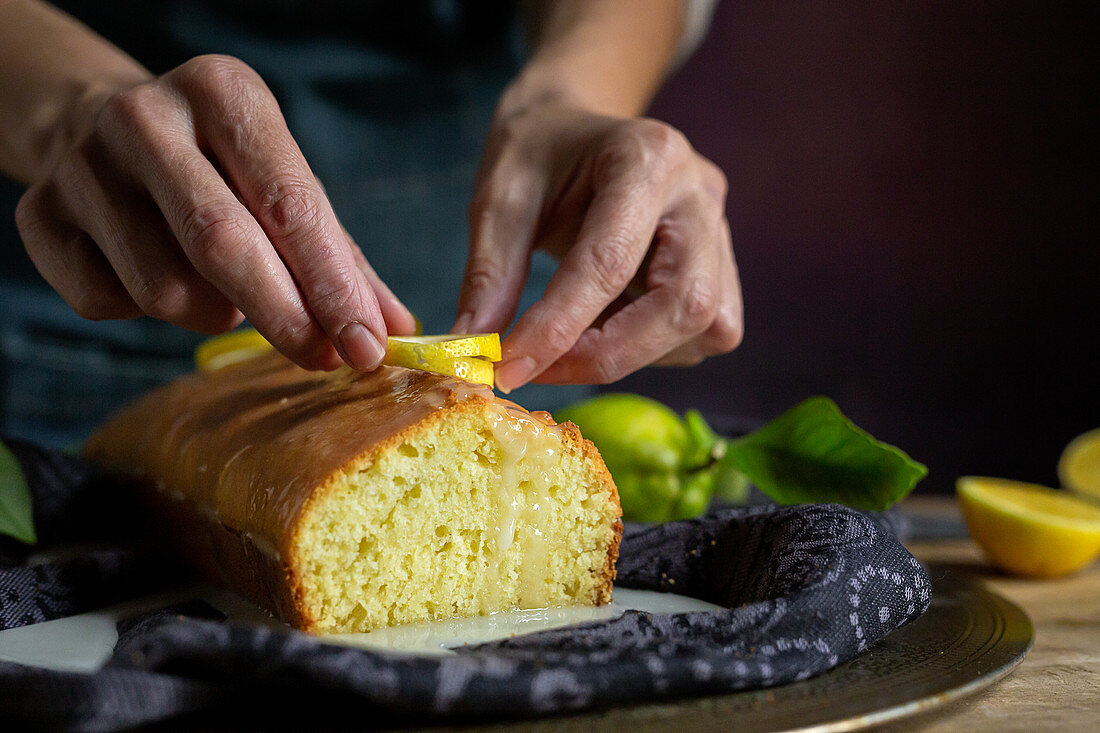 Preparing a homemade delicious lemon cake covered with glaze and lemon slices