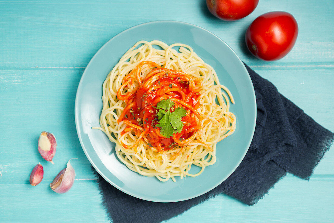 Blue ceramic plate with pasta and tomato sauce decorated with parsley and basil
