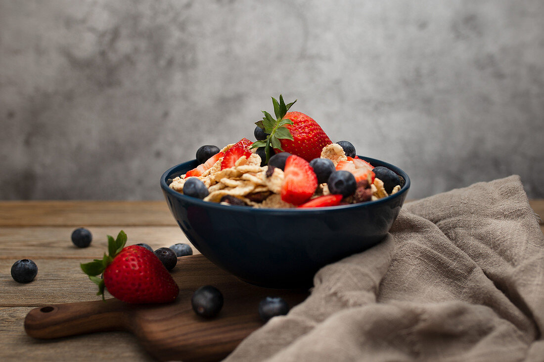 Breakfast bowl of corn flakes with strawberries and blueberries