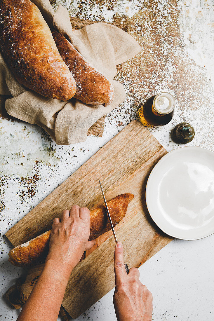 Cutting golden baked bread on wooden board on rustic surface