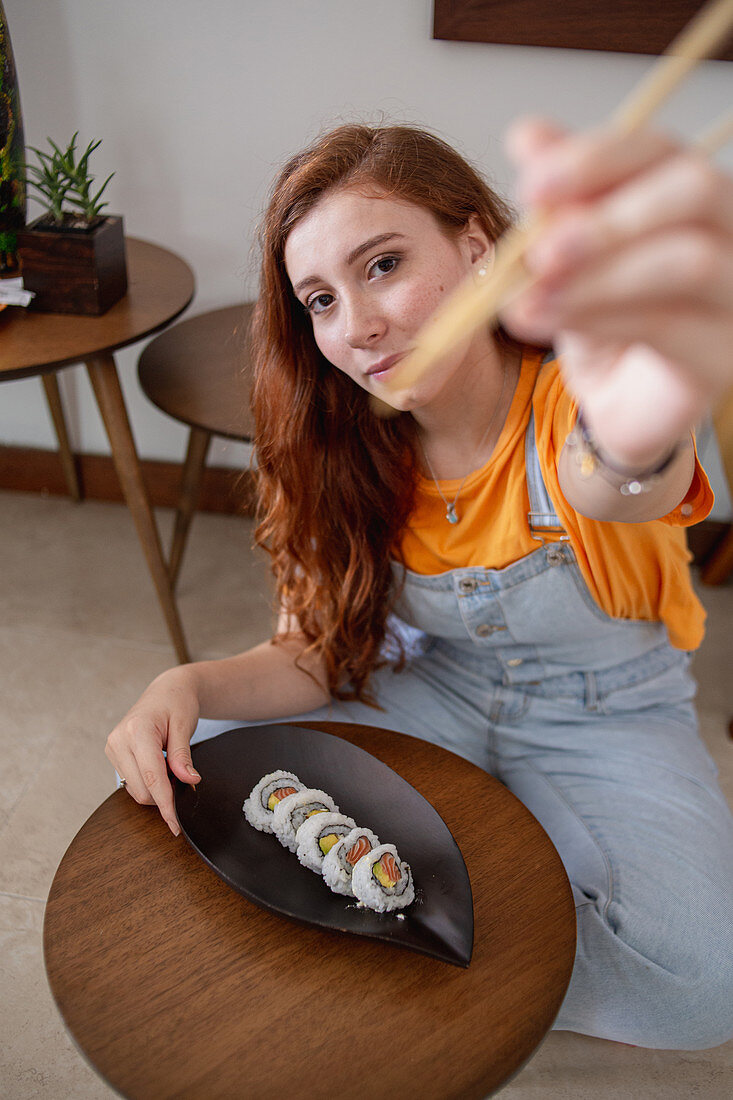 Young redhead woman in casual clothes looking at camera using chopsticks while sitting at table and eating sushi at home
