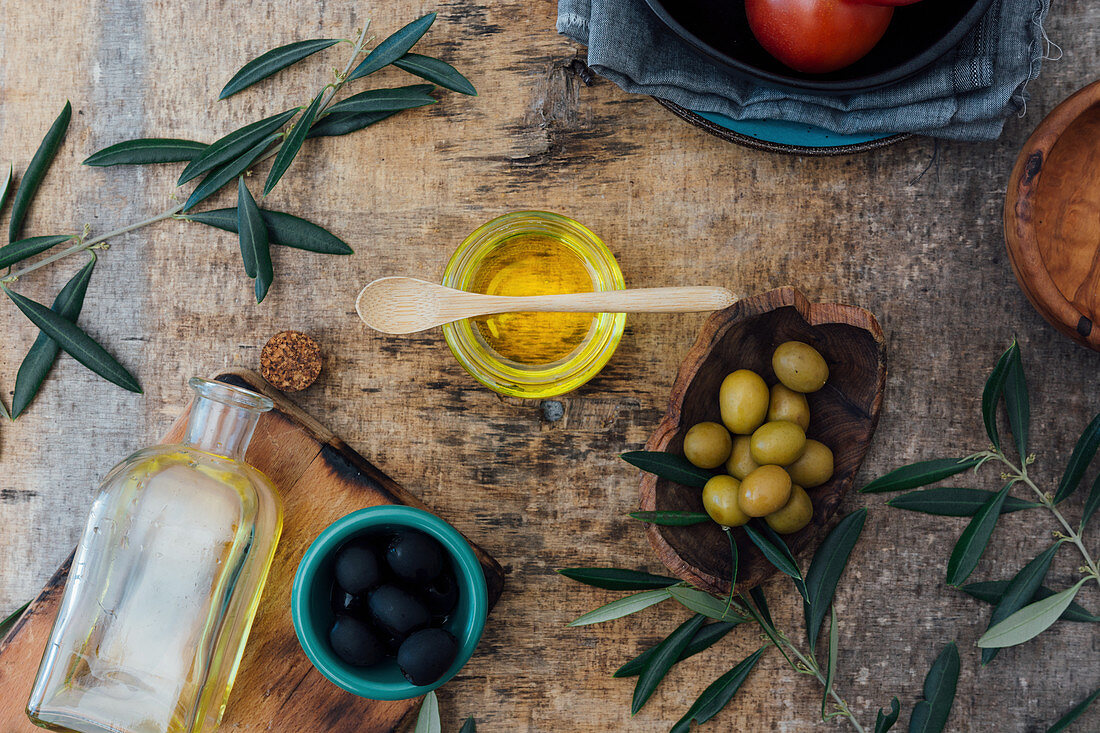 Glass jar with organic olive oil with wooden spoon on gray table with fresh tomatoes green and black olives