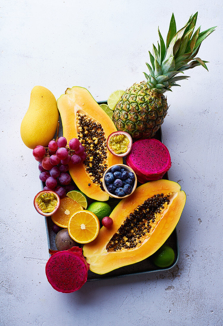 Tropical fruits flat lay with mango, papaya, pitahaya, passion fruit, grapes, limes and pineapples on a tray