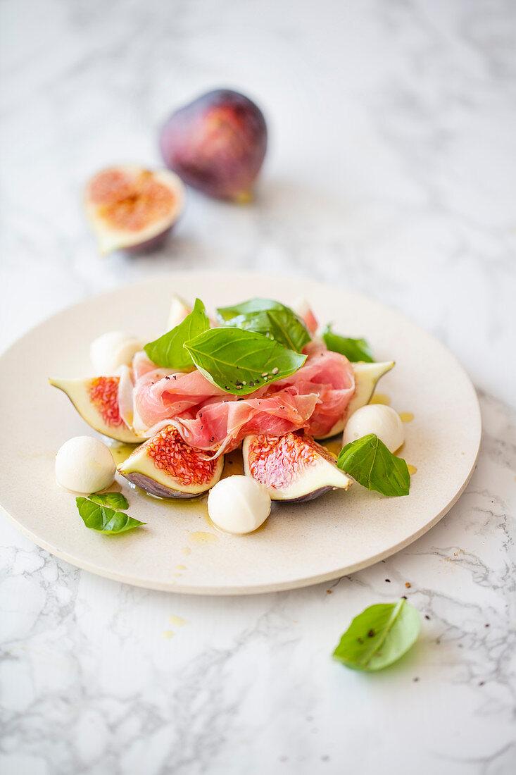 Salad with fresh figs, mozzarella, parma ham and basil