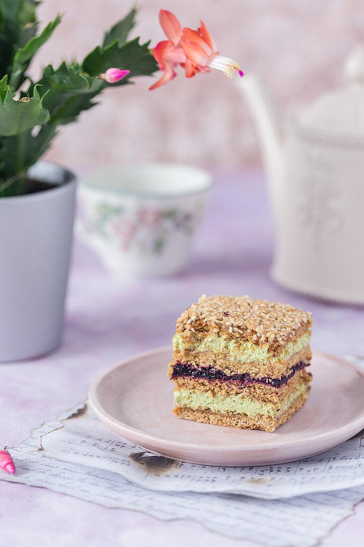 Sesame and honey cake with pistachio cream and blackcurrant jam