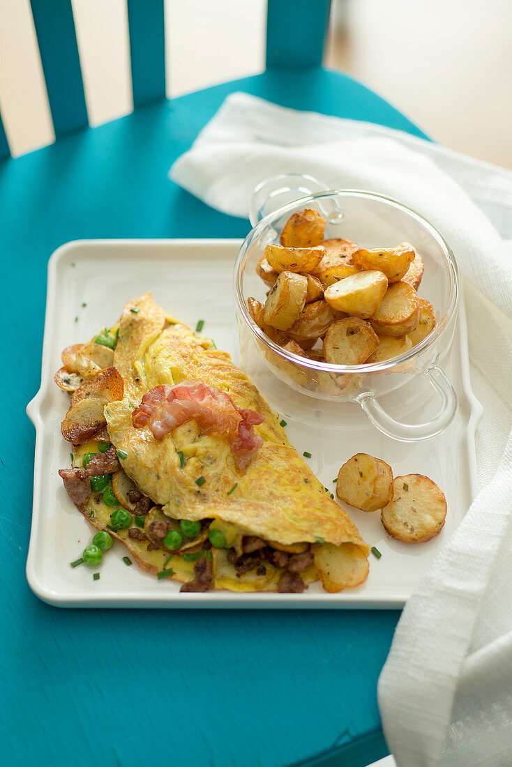 Omelette with fried potatoes, bratwurst and bacon