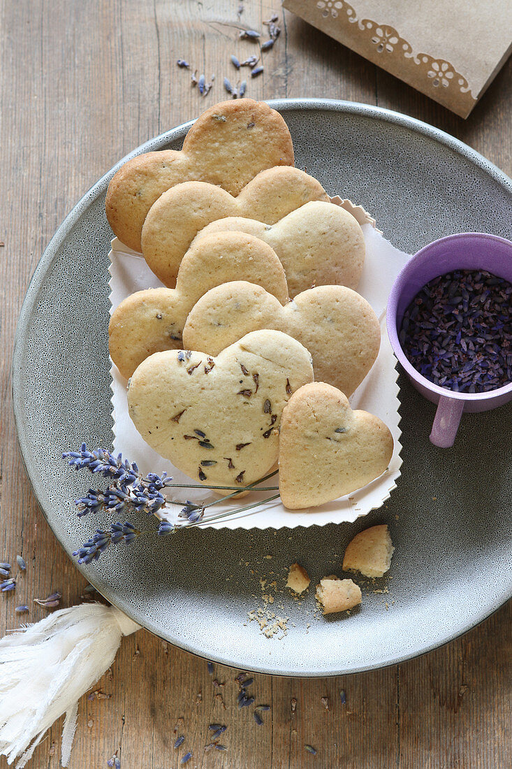 Heart-shaped, gluten-free lavender shortbread biscuits in a cardboard dish