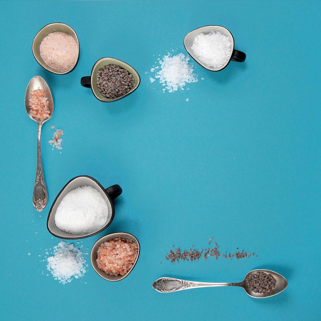 Different types of salt on blue background