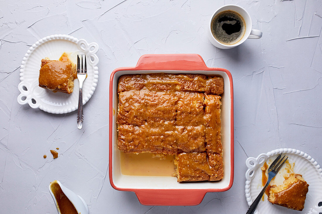 Tres Leches cake in baking tray, covered with caramel sauce and sprinkled with sea salt