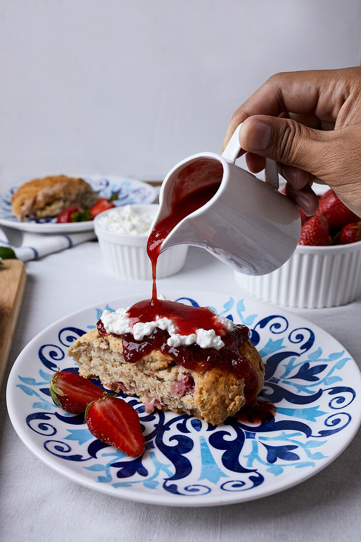 Drizzling strawberry sauce over scones served with cottage cheese and jam