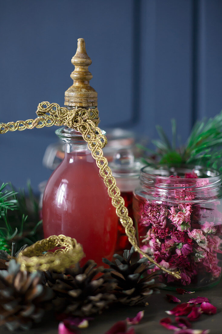 Homemade liqueur and dried flowers in jars as Christmas presents
