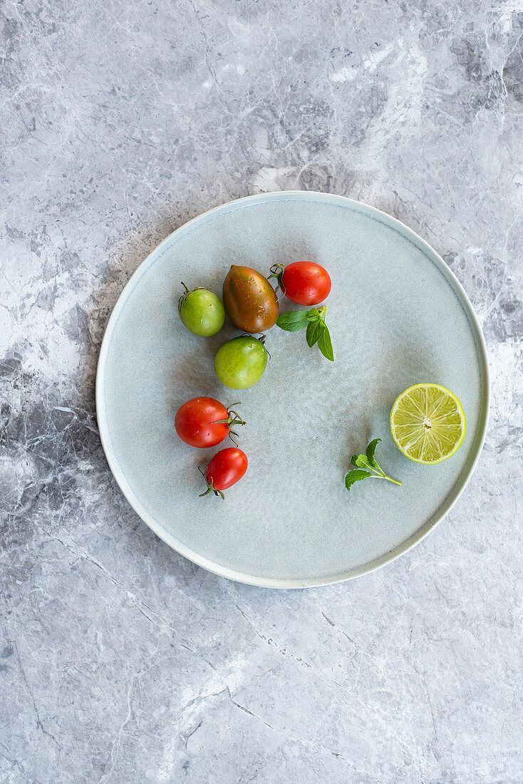 Various tomatoes and half a lime on a plate