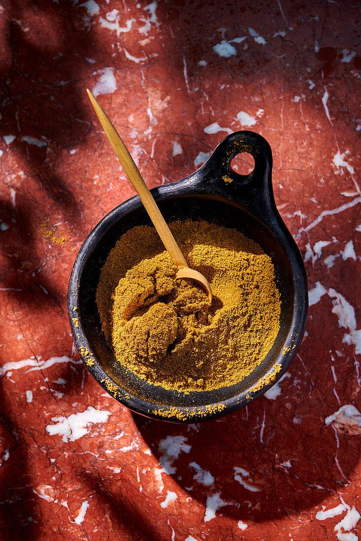 Ras el hanout in a dish with a spoon