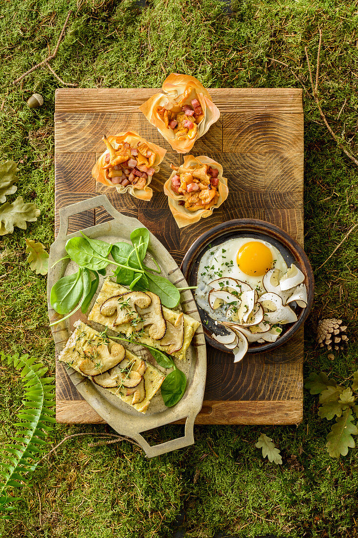 A fried egg with porcini mushrooms, potato and porcini mushroom cake and chanterelle and bacon baskets