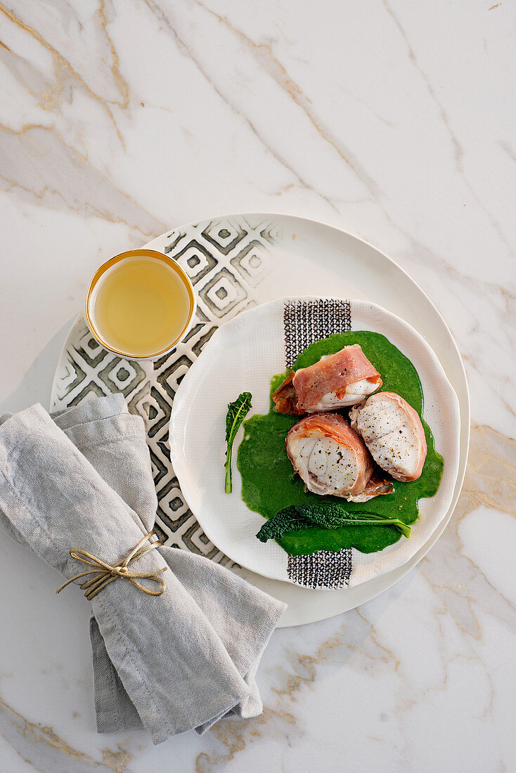 Monk fish wrapped in ham on Tuscan kale cream