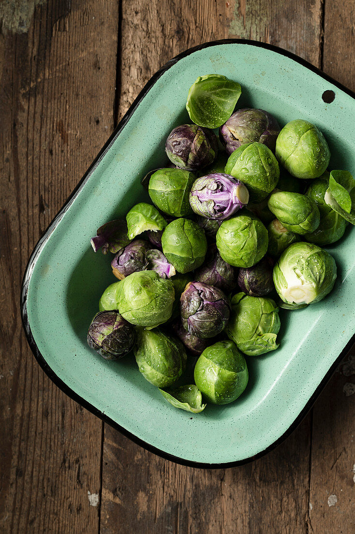Raw Brussel sprouts in a vintage, green enamel dish, on a rustic wooden surface.