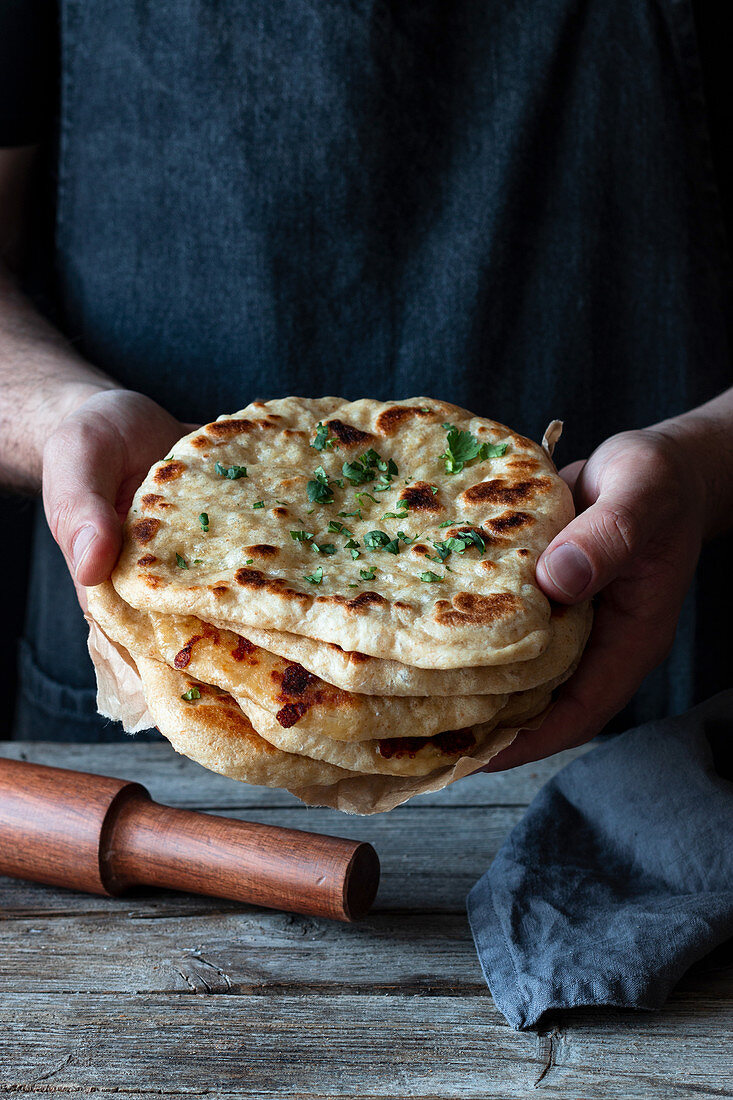 Unrecognizable man holding stack of fresh naan flatbread over lumber table in rustic kitchen