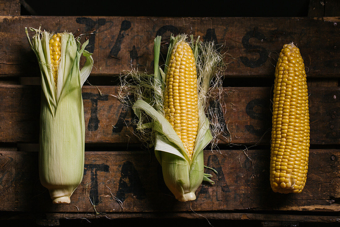 Top view of steps of fresh ripe corn peeling on wooden table