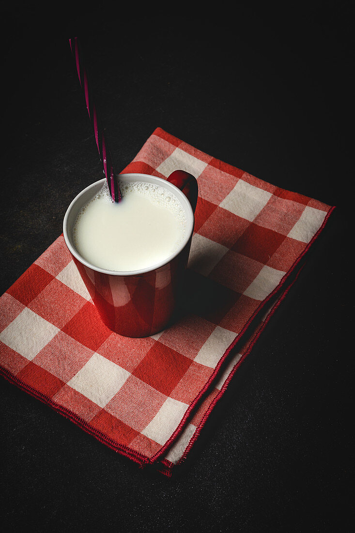 Cup of white milk with bright striped straw on table over black background and checkered towel