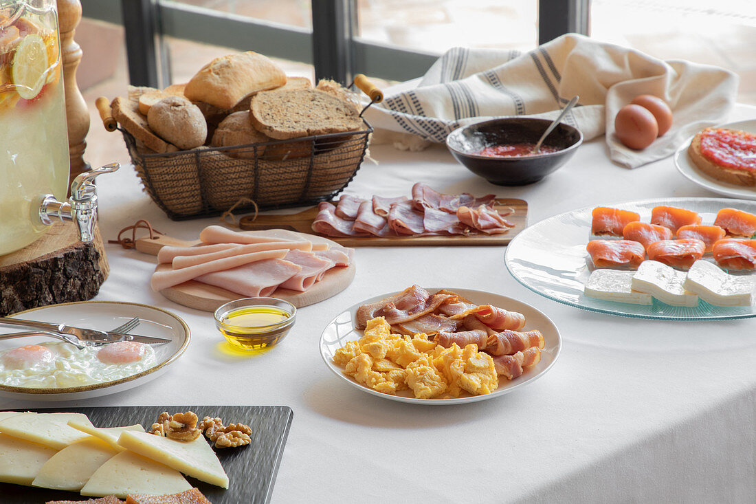 From above view of cozy table setting consisting of fried eggs and bacon salmon cheese meal and bakery at home