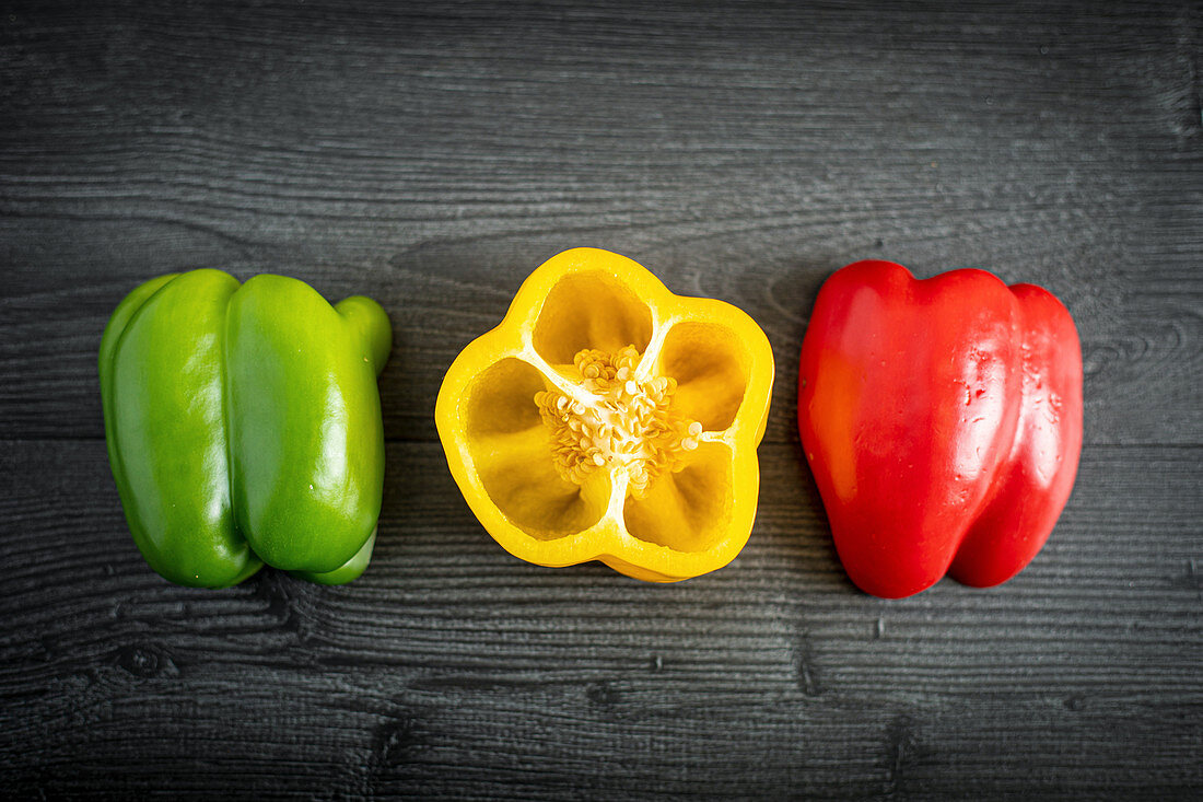 From above appetizing fresh sliced green red yellow pepper on gray surface