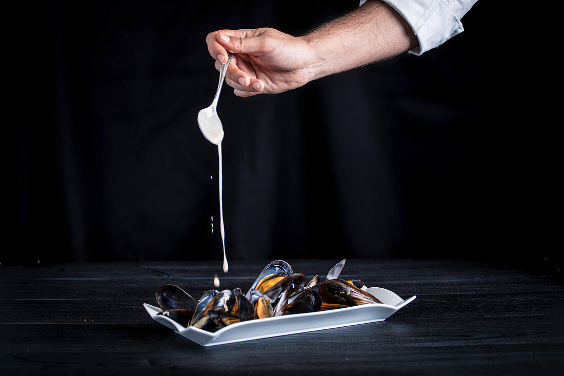 Crop cook pouring fragrant appetizing mussels with Thai sauce on black background