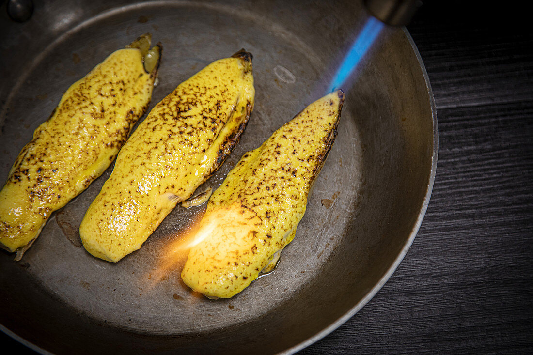 Crop person directing burner to pan with juicy endive preparing in frying pan on gray background