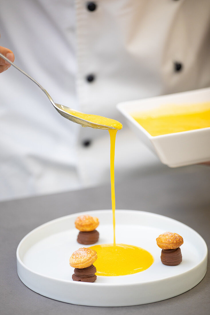 Koch träufelt Orangensauce auf Teller mit Schokoladengebäck