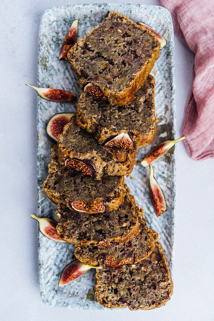 Fig bread recipe with banana, fresh figs and walnuts sliced on a rectangular plate.